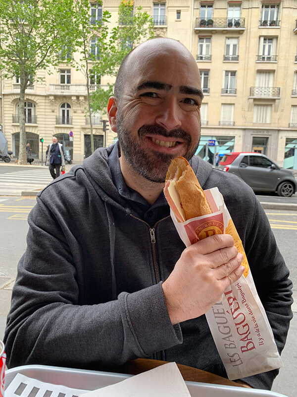 Mark eating a baguette sandwich in Paris
