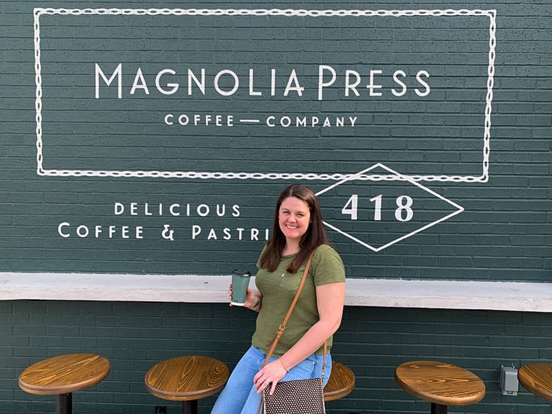 Barbara outside of Magnolia Press in Waco, TX with a cup of Texas Pecan coffee
